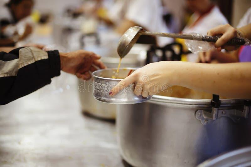 O os sem-abrigo pegara o alimento da caridade dos doadores do alimento na sociedade: pobreza do conceito fotografia de stock royalty free