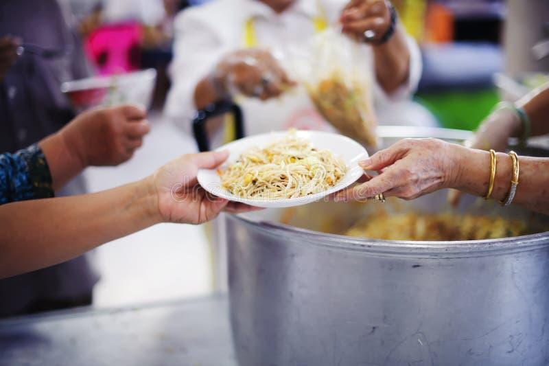 O os sem-abrigo pegara o alimento da caridade dos doadores do alimento na sociedade: pobreza do conceito foto de stock royalty free