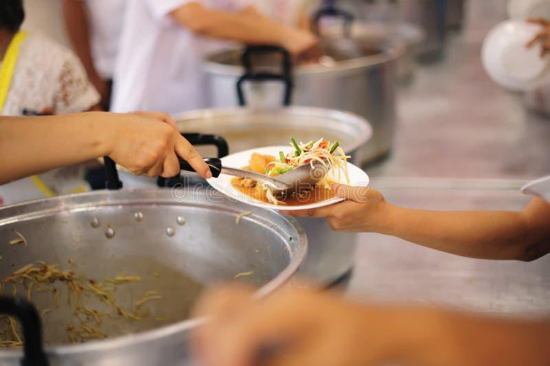 O os sem-abrigo pegara o alimento da caridade dos doadores do alimento na sociedade: pobreza do conceito foto de stock