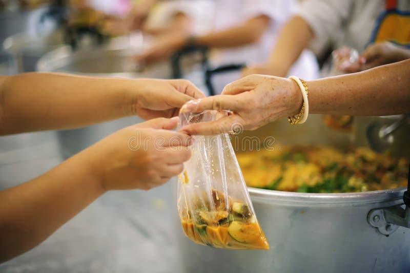 O os sem-abrigo pegara o alimento da caridade dos doadores do alimento na sociedade: pobreza do conceito imagens de stock royalty free