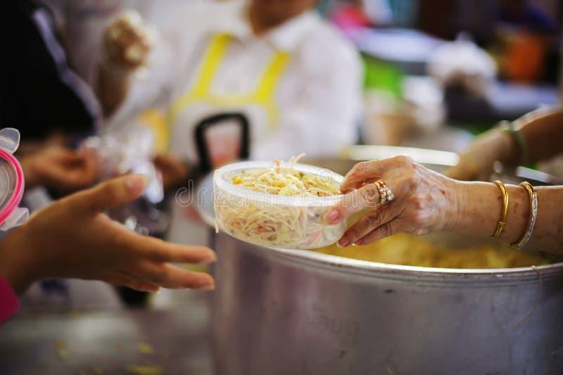O os sem-abrigo pegara o alimento da caridade dos doadores do alimento na sociedade: pobreza do conceito fotos de stock