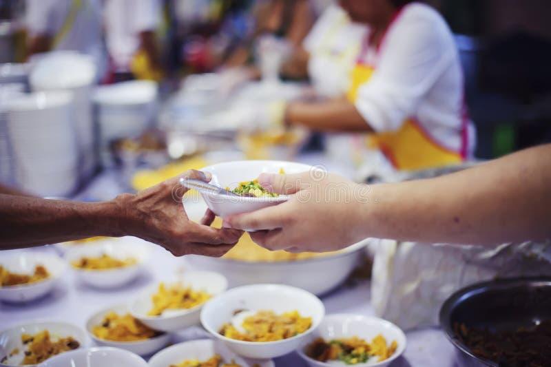 O os sem-abrigo pegara o alimento da caridade dos doadores do alimento na sociedade: pobreza do conceito imagem de stock
