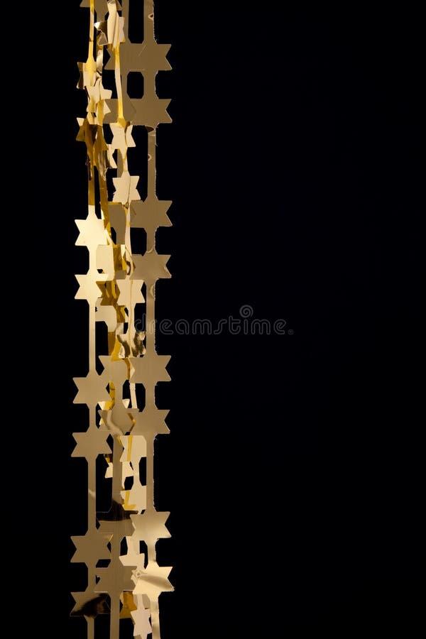 O ouro da decoração do Natal stars festões imagem de stock