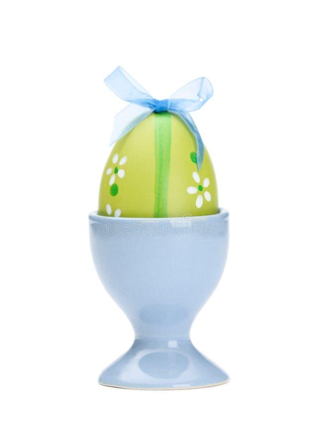 O ovo da páscoa colorido verde está no copo de ovo fotos de stock