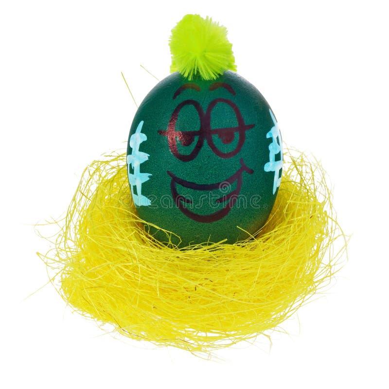 O ovo da páscoa, feito a mão pintado em uma cara de sorriso dos desenhos animados, senta-se na fotos de stock