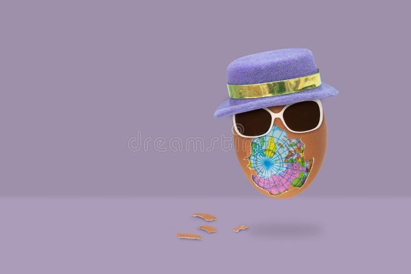 O ovo descascado tem um globo para dentro com vidros e o chapéu está voando no fundo roxo fotografia de stock royalty free
