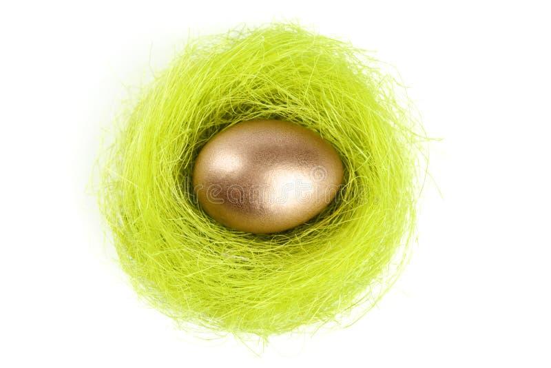 O ovo dourado está no ninho da fibra do sisal imagens de stock