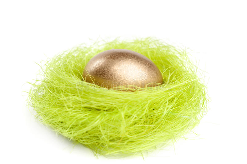 O ovo dourado está no ninho da fibra verde do sisal foto de stock royalty free