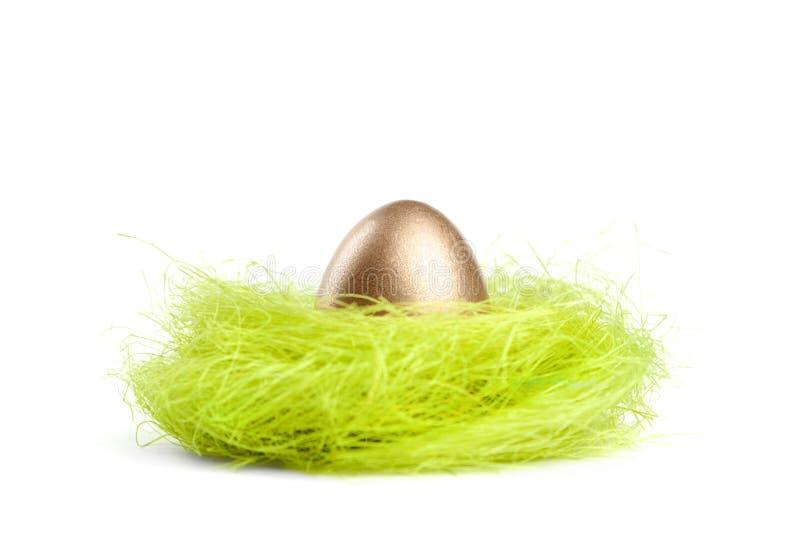 O ovo dourado está no ninho do material do sisal imagens de stock