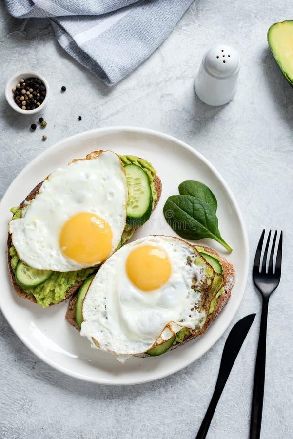 O ovo frito, o abacate e o pepino na grão inteira brindaram o pão fotos de stock