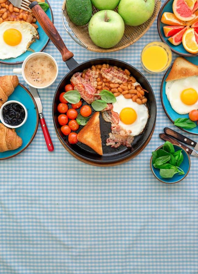 O ovo frito, feijões, tomates, bacon, brinda vários frutos, suco, fotografia de stock
