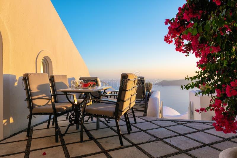 O pátio com a tabela e as cadeiras decoradas com buganvília bonita floresce na ilha de Santorini, Grécia fotos de stock royalty free