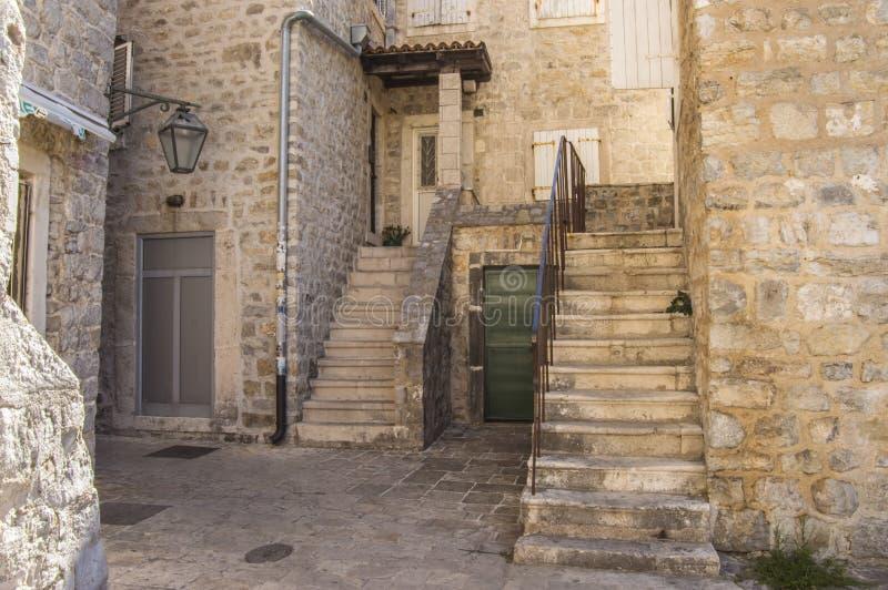 O pátio de uma das casas na cidade velha de Budva, Montenegro com escadas fotos de stock