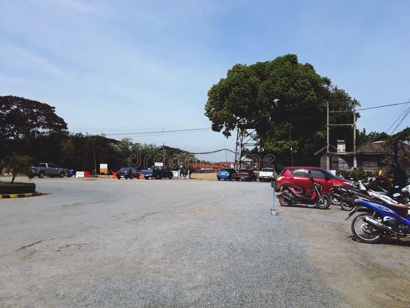 O pátio exterior tem uma grande árvore e há muitos parques de estacionamento Fundo do céu fotos de stock