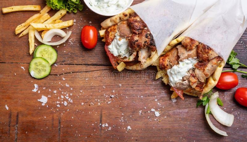 O pão árabe do giroscópio, shawarma, leva embora, alimento da rua Turco grego tradicional, alimento da carne na tabela de madeira imagem de stock