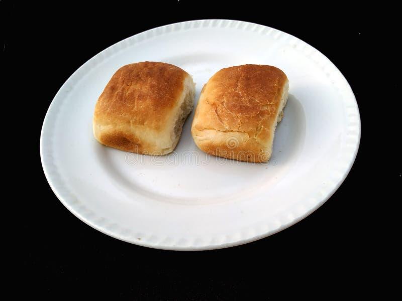 O pão, ícone da padaria, cortou o pão integral fresco isolado no fundo preto fotos de stock
