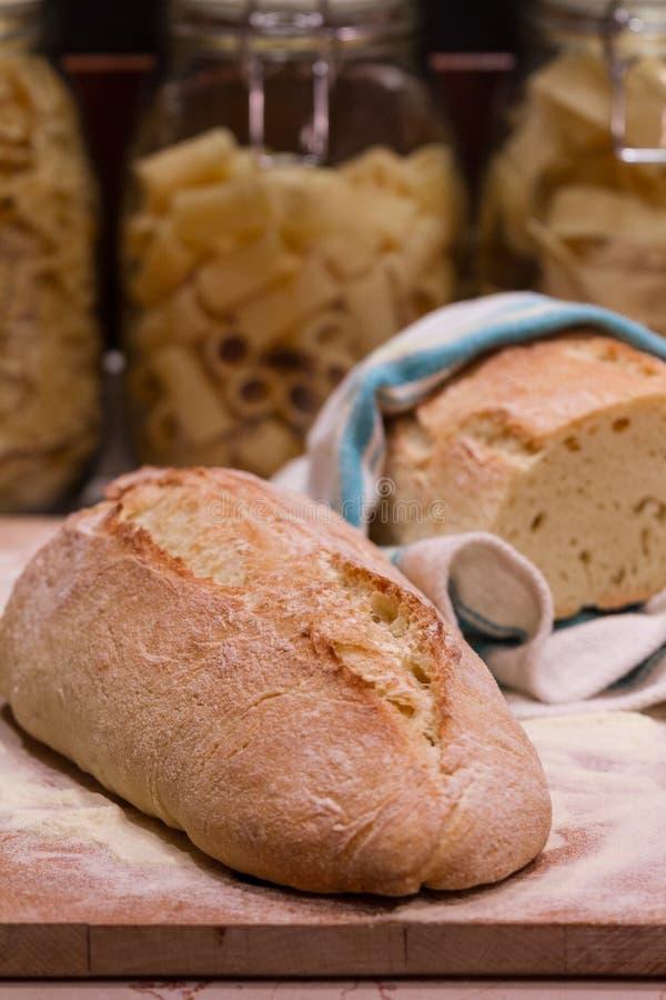 O pão colocou em uma placa de desbastamento, com as bacias da massa no backgrou fotos de stock