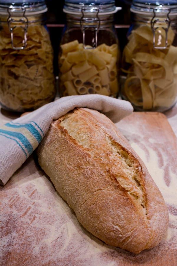 O pão colocou em uma placa de desbastamento, com as bacias da massa no backgrou fotografia de stock