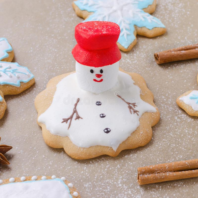 O pão-de-espécie do Natal gosta de derreter o boneco de neve, os flocos de neve e a farinha como a neve no papel do cozimento imagens de stock