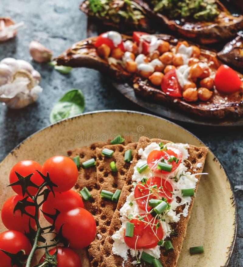 O pão de Rye brinda com queijo de cabra, tomates, plântulas na placa no fundo azul com brinde cozido da batata doce foto de stock royalty free