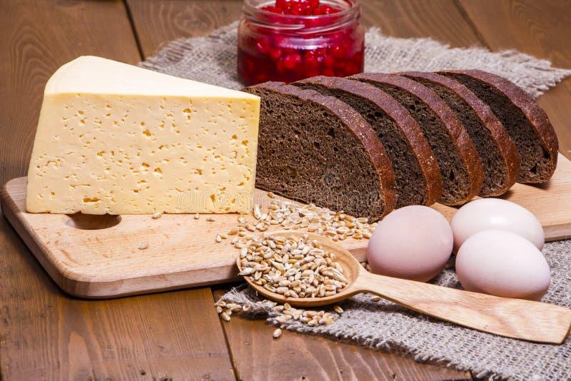 O pão e o queijo de Rye no fundo do despedida, grões do trigo, eggs o close-up fotografia de stock