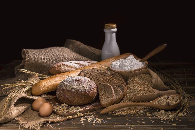 O pão integral, o leite, a farinha e o pano inteiros ensacam na tabela de madeira imagens de stock
