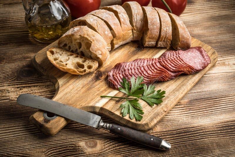 O pão italiano do ciabatta cortou nas fatias com salame foto de stock royalty free