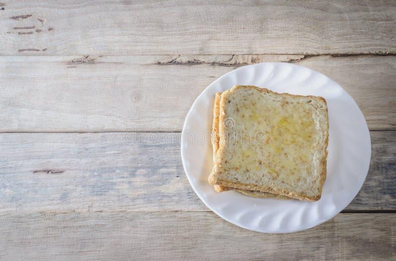 O pão no prato branco pôs sobre a mesa de madeira foto de stock