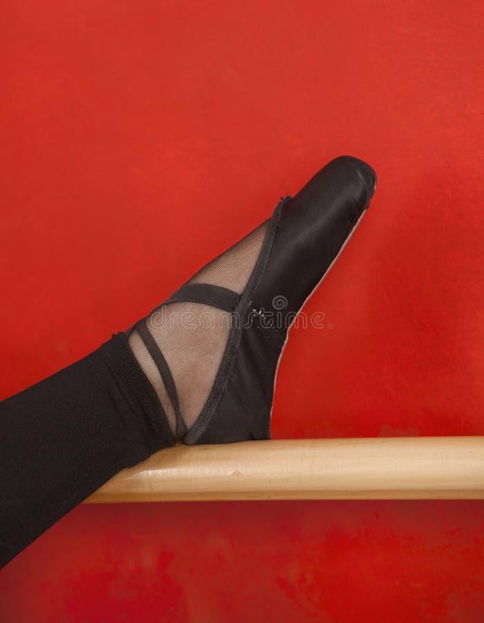 O pé da bailarina em Barre Against Red Wall foto de stock