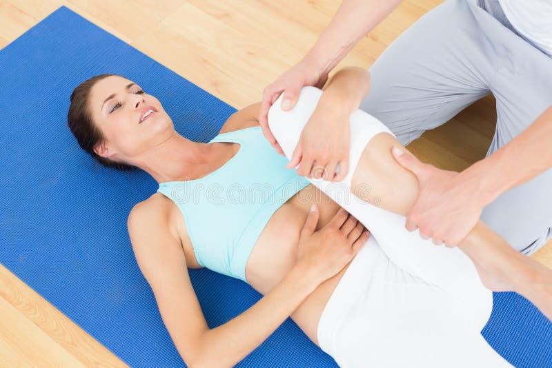 O pé da jovem mulher de exame do fisioterapeuta fotos de stock royalty free