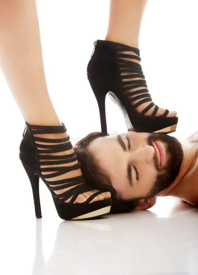 O pé da mulher na cara do homem foto de stock