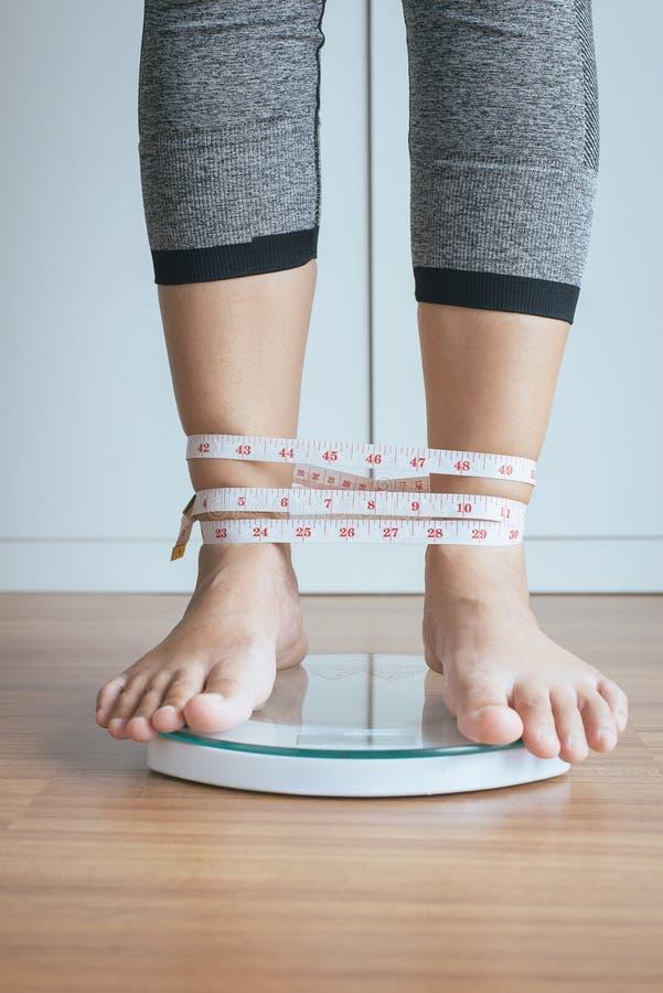 O pé da mulher que está em eletrônico pesa escalas com fita métrica do pé sem fôlego imagens de stock