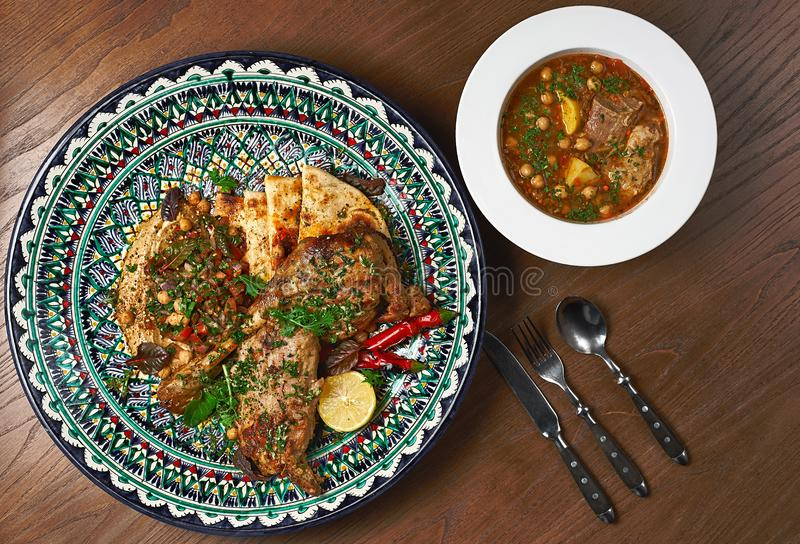 O pé de cordeiro cozeu com molho em uma placa cerâmica, com um hummus decora Sopa do cordeiro de lentilhas vermelhas imagem de stock