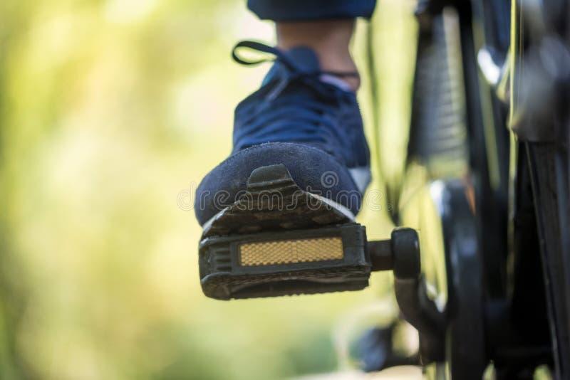 O pé de uma pessoa que monta uma bicicleta fora imagens de stock