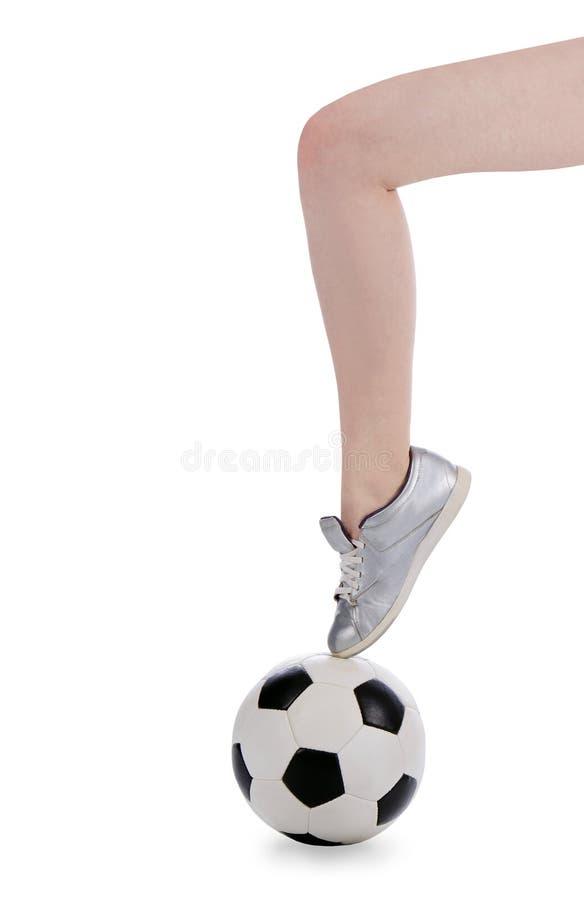 O pé fêmea na sapata está na esfera de futebol imagem de stock
