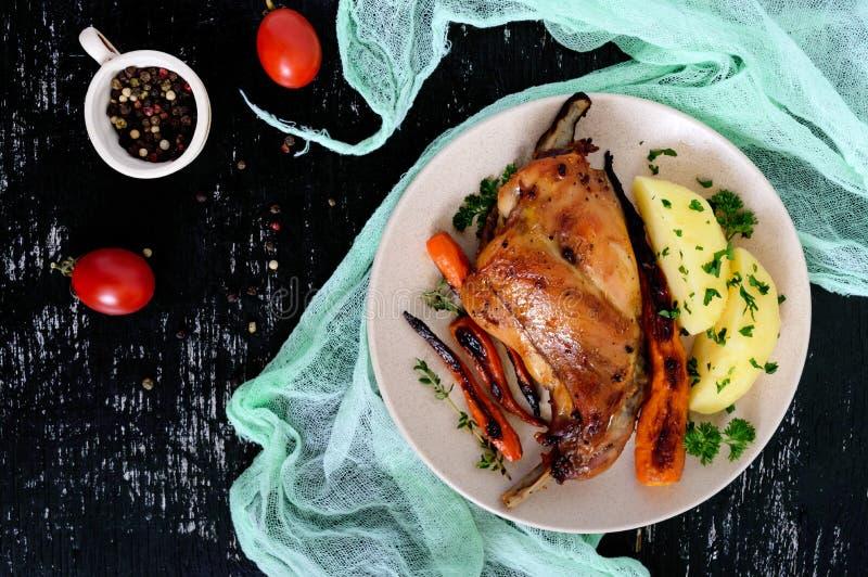 O pé fritado do coelho, decora das batatas fervidas, cenouras grelhadas - em uma placa em um fundo escuro foto de stock