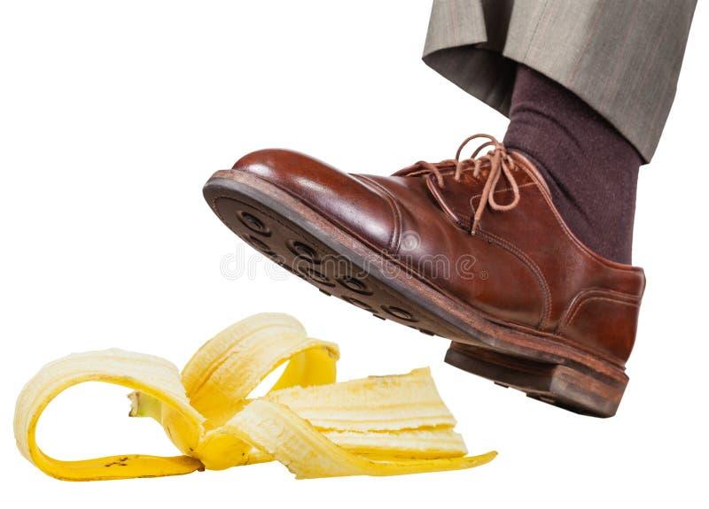 O pé na sapata marrom esquerda desliza em uma casca da banana fotos de stock royalty free