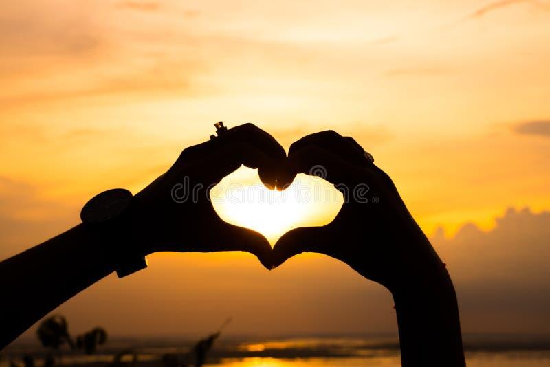 O pôr do sol feroz com ambas as mãos faz coração foto de stock