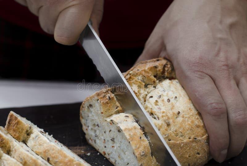 O p?o inteiro da gr?o p?s sobre a placa de madeira da cozinha com um cozinheiro chefe que guarda a faca do ouro para o corte imagens de stock