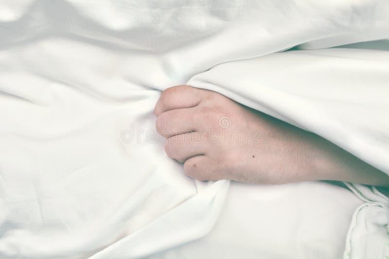O paciente criticamente doente abraça a folha de cama na mão fotos de stock
