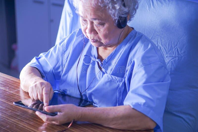 O paciente idoso superior asiático da mulher da senhora idosa que guarda à disposição a tabuleta digital leu o quando do e-mail e foto de stock