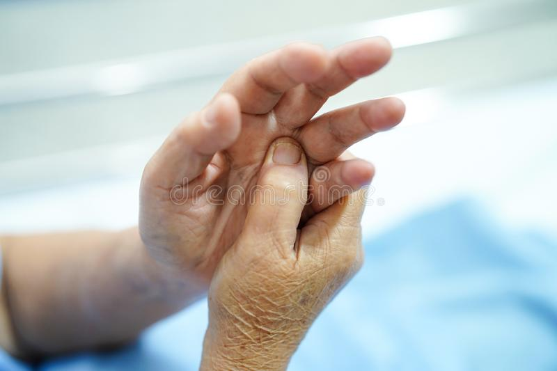 O paciente superior ou idoso asiático da mulher da senhora idosa sente a dor sua mão na cama na divisão de hospital de nutrição:  imagem de stock