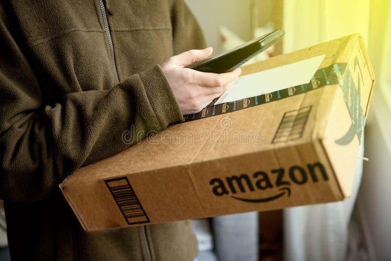 O pacote da exploração da mulher da entrega do pacote de UPS das Amazonas em linha ret foto de stock royalty free