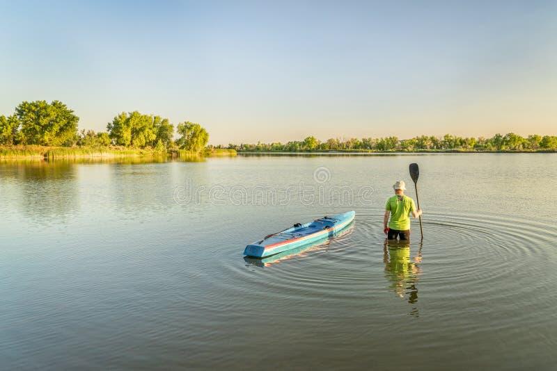 O paddler masculino com levanta-se o paddleboard imagens de stock royalty free