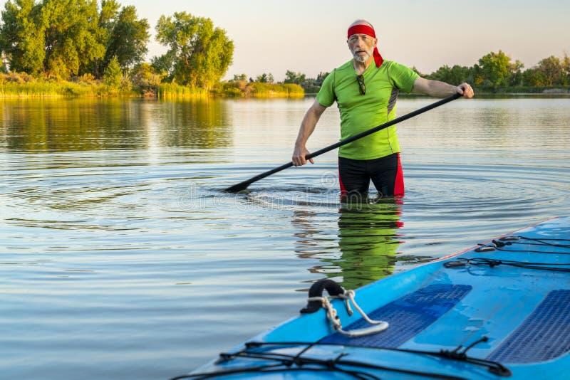 O paddler superior com levanta-se o paddleboard fotografia de stock royalty free