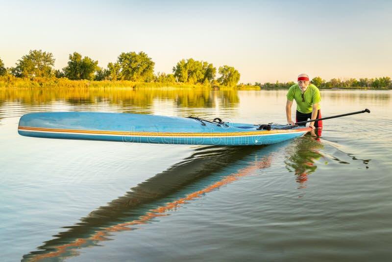 O paddler superior com levanta-se o paddleboard imagem de stock
