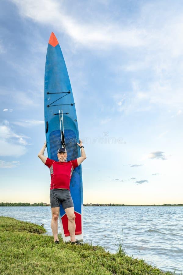 O paddler superior com seu levanta-se o paddleboard imagem de stock