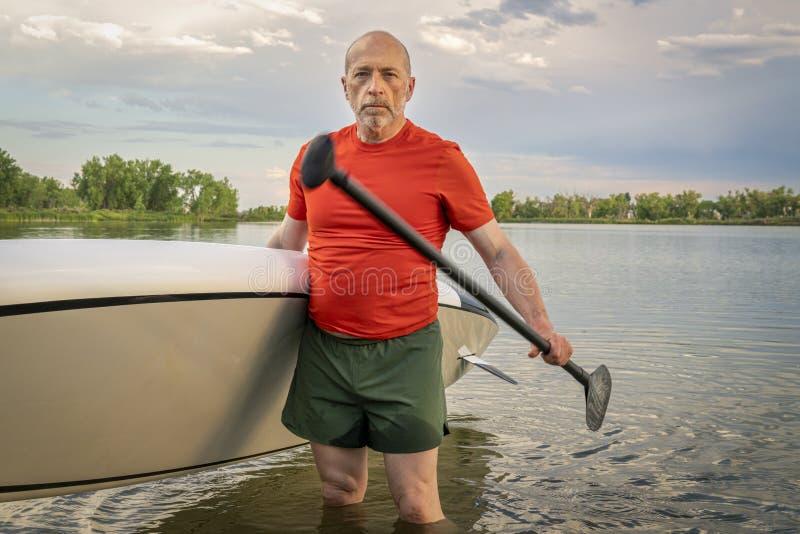 O paddler superior com seu levanta-se o paddleboard fotografia de stock royalty free