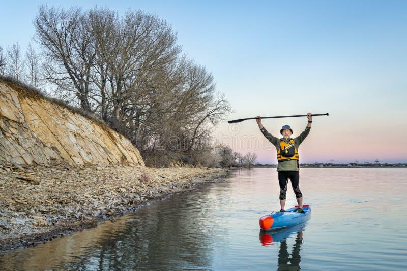O paddler superior levanta-se sobre o paddleboard imagem de stock