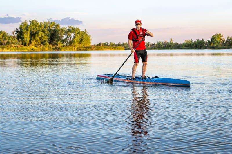 O paddler superior levanta-se sobre o paddleboard fotografia de stock
